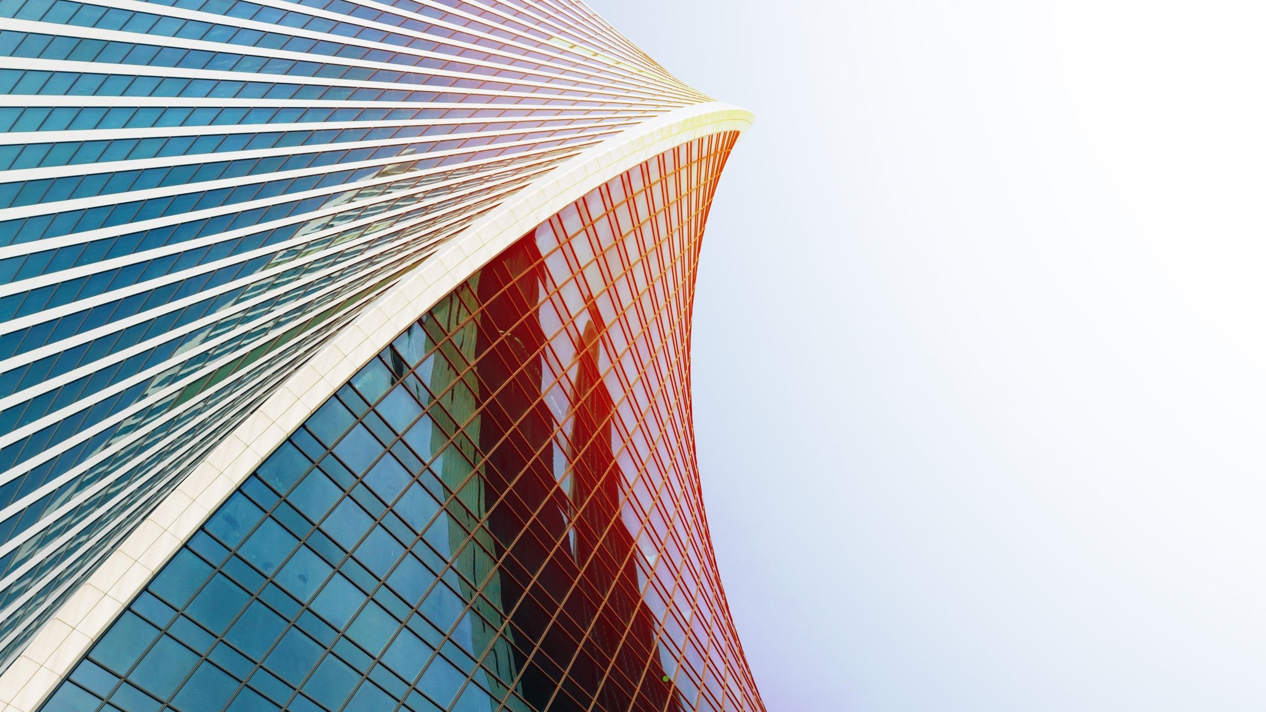 View looking up at a curved skyscraper.