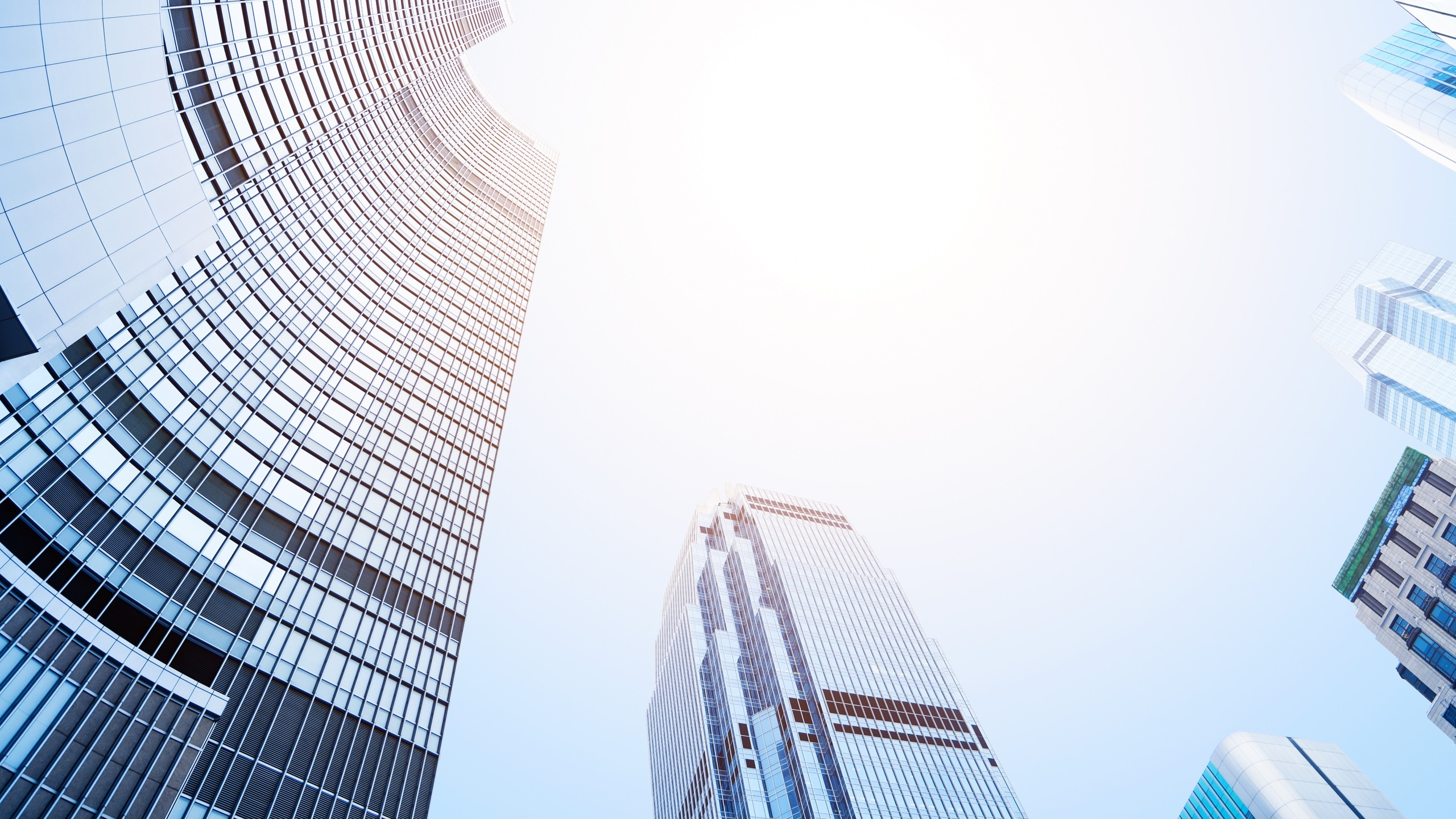 View looking up in the center of multiple tall buildings.