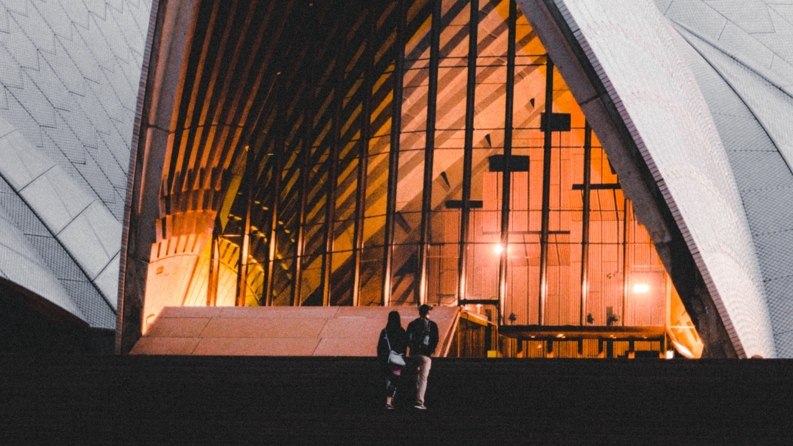 Couple walking into the Sydney Opera House.