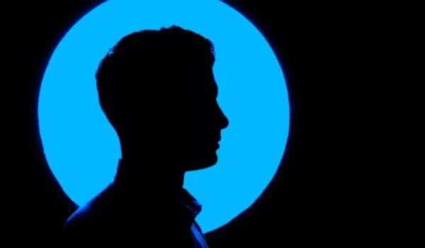 Shadow of a man in front of a bright blue circle.