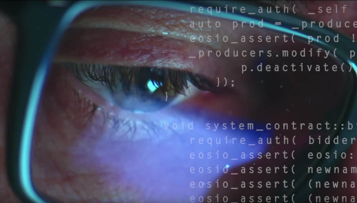 Dramatic close up shot of a mans eyeglasses with coding overlaid on the image.